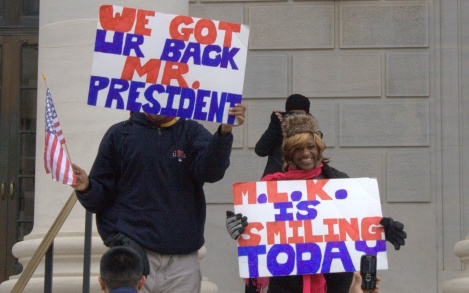 "Two viewers hold up signs saying ""We got your back Obama"" and ""MLK is Smiling Today"". Photo by Gabrielle A. Wright."