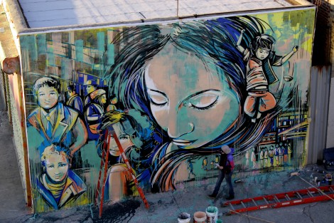 Artist Alice Pasquini is shown painting her latest mural. She traveled from Rome to be a part of the magnetic Bushwick art scene. Photo by Gabrielle A. Wright.